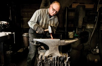 Mark Hangas forges the edge of a knife blade with a hammer and anvil. Mark has been making knives since 1976 when he joined his father and grandfather.