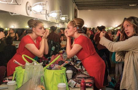 "The women's dressing room bustles before a performance of ""West Side Story."""
