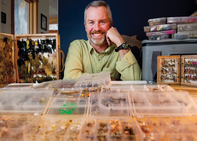 """When fly-fishing guide Tom Jenni thinks about climate change, he thinks about the effects of those changes on bugs, because his business depends on them. """"I plan my season around hatches, I plan my boxes around those hatches,"""" said Jenni as he pulled out box after box of flies organized by type and season. Photo by Jeremy Lurgio"""