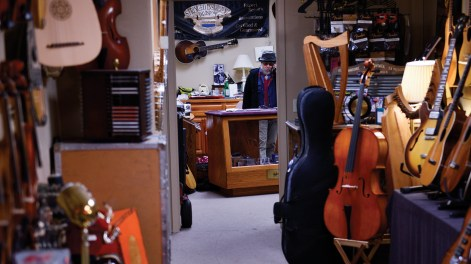 Peter answers a phone at his shop, the Stringed Instrument Division in Missoula, Montana. The shop features all kinds of instruments including a few rare guitars. A 1927 L-1 flattop that Robert Johnson played hangs on the wall behind the luthier.
