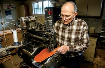 Vic Hangas sews a knife sheath with the 1910 Landis sewing machine that his father-in-law, Rudy Ruana, bought when he started making the sheaths himself.