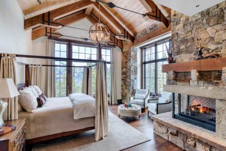 """""""The master bedroom has a lot of natural light and views in two directions. The corner fireplace anchors the room and has artisan metal accents,"""" said Brooks. """"The softness and lightness of fabric contrasts the stone, wood, and iron,"""" added Bing."""