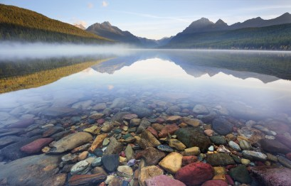 The river rocks in Bowman Lake form an underwater mosaic in the early morning light.