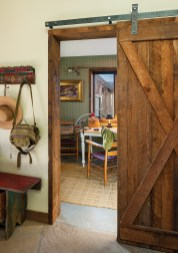 A sliding barn door echoes the agricultural roots of the Shields Valley in the entryway. The rustic antique bench and hooks were purchased by the owner at Round Top Antiques Fair in Texas.