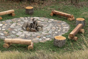 An outdoor, hand-laid fire pit is encircled by customcrafted wooden seats.