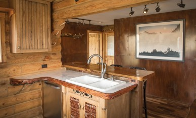 The kitchen features antlers, willows from nearby Miner Creek, and marble countertops. Hanging on the wall in the background is Reece's lithograph, Call of the Wild, which is also the home's name.