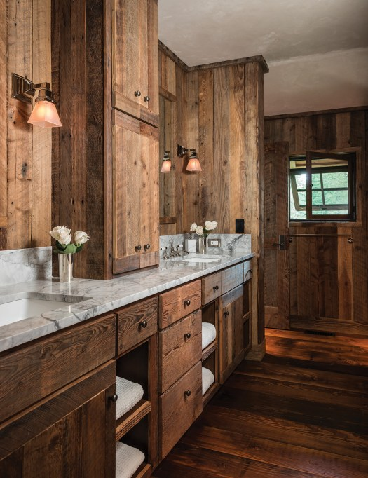 Continuing the material palette from the exterior to the interior, Ankeny Construction Management expertly incorporated reclaimed wood in the bathrooms and bedrooms. Carrera marble countertops in the bathroom lighten the space, while in the bedroom, off-white plaster highlights the mullioned windows.