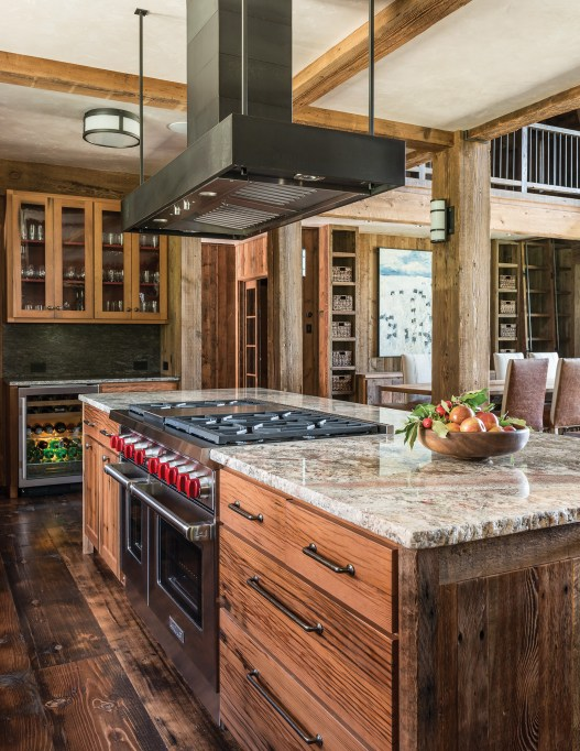 In the kitchen, a custom-made hood reinforces the steel palette that accents structural joinery throughout the house. Reclaimed pickle barrel cabinetry punctuates the color of the granite countertops