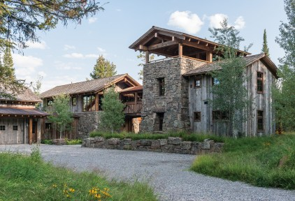 Hand-picked stone stacked to accent different sections of the adjoined buildings adds visual contrast to the vertical lines established by the reclaimed wood siding.