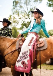 Miss Rodeo Montana 2013, Alyson Grinestaff of Bozeman, watches the action near the grandstands after riding around the arena at full speed, waving to the crowd.