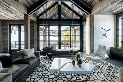 The design team worked together to artfully combine steel elements with rustic, reclaimed timber. The home's design showcases the building materials, allowing sleek lines and tough surfaces to act as decoration. The floating sofa in the great room was the idea of interior designer John Vancheri.