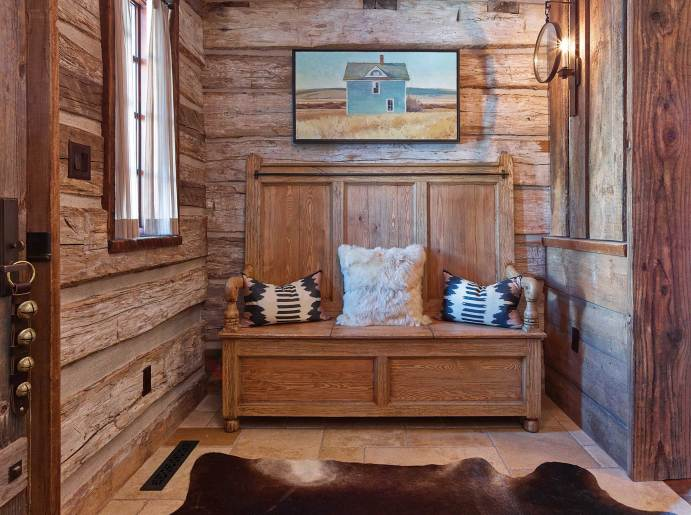 In the foyer, an antique-style Ralph Lauren settle with baby alpaca and custom pillows accents the reclaimed wood on the walls. Cashmere curtains allow soft daylight to filter into the space where a Jared Sanders painting connects to Wyoming's landscape.
