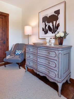 A French Provincial antique-inspired chest of drawers and chair brings elegant sophistication into the room.