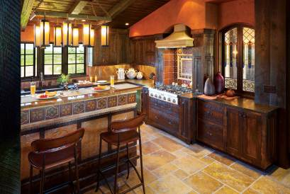 The rustic kitchen, with dark wood cabinetry from Iowa bridge planks, is accented by ceramic mosaic tiles and hammered copper.