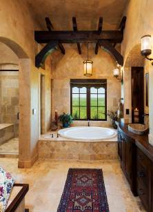 The master bath is a masterpiece of the Templeton home, crowned with dark wood beams and patterned in travertine.