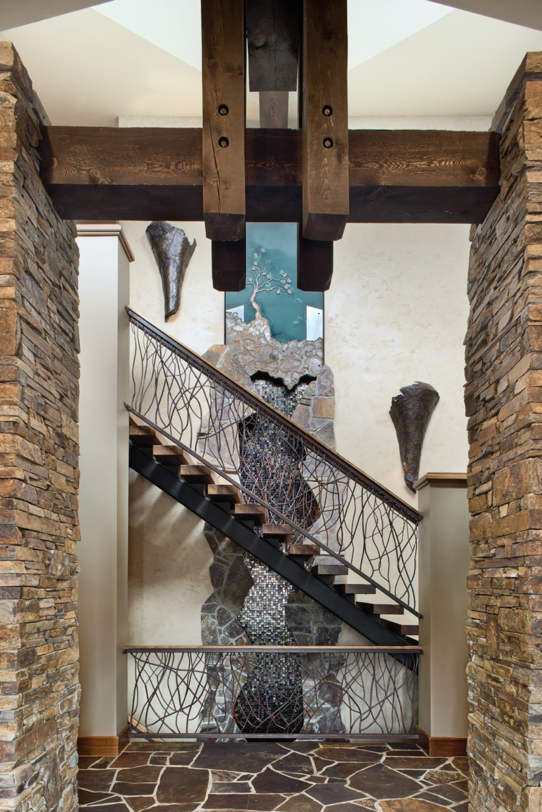 The front entry of the home offers a custom-made water feature that leads upstairs. The home's design wraps around the second-floor staircase.