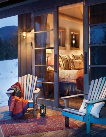 Vintage wooden doors connect the bedroom to a cozy porch with a lakefront view.