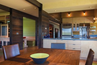 """Fernau designed a mobile dining room table with wheels, a number of different shaped leaves, and a mix of hardwoods to accommodate big or small dinners. """"When it's put together, it creates different patterns,"""" he says. The kitchen features maple cabinets and soapstone countertops."""