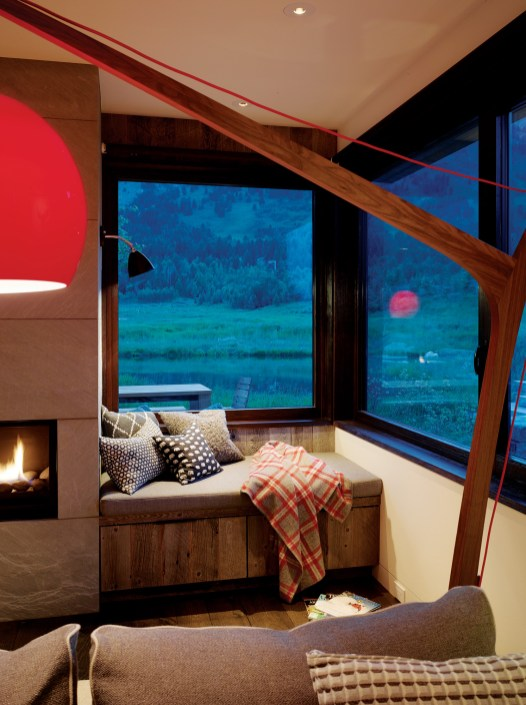 A cozy fireplace and a cuddly nook in the den provides a comfortable place to snuggle up with a book after a day on the slopes