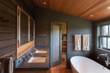 The master bathroom, like the rest of the home, is clean and simple in design, with modern sensibilities and fixtures.