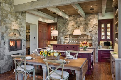 In the kitchen the coziness of the hearth brings family and guests together in an intimate space tucked in from the great room by a lowered ceiling and a cloister of stacked stone.