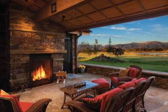 The outdoor patio offers warmth on a cool Montana evening. The horizontal stonework is indicative of a Frank Lloyd Wright Prairie home.