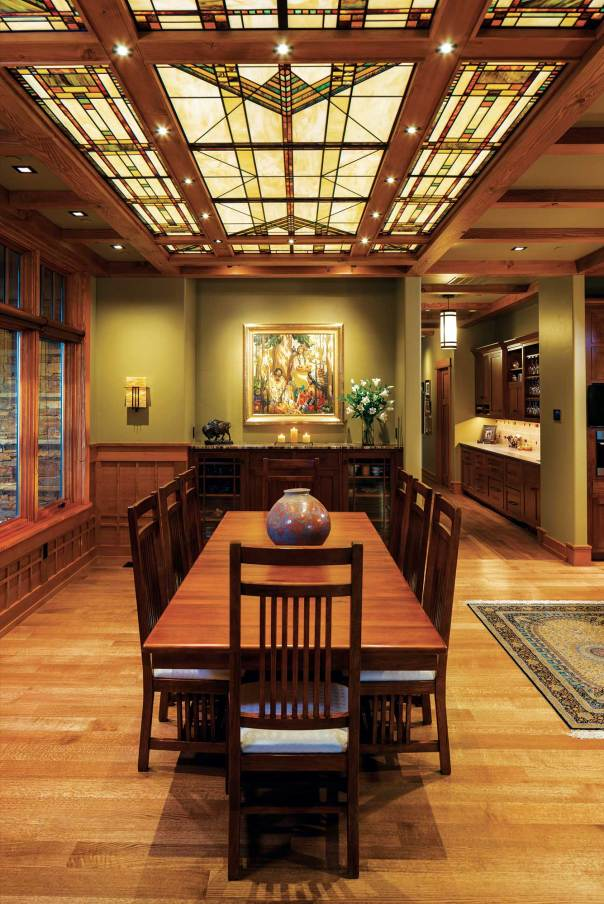 The dining room looks out toward a mountain vista with an overhead, stained-glass ceiling lighting the Missionstyle furniture.
