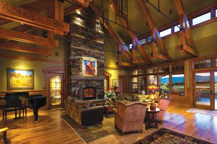 Rafters repeat the design of the stained glass motif placed throughout the home, while the fireplace highlights the horizontal stonewr ight on targe t work that is repeated outdoors.