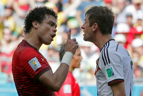 Portugal's Pepe, left, argues with Germany's Thomas Mueller after they clashed during the group G World Cup soccer match between Germany and Portugal at the Arena Fonte Nova in Salvador, Brazil, Monday, June 16, 2014.  (AP Photo/Matthias Schrader) Brazil Soccer WCup Germany Portugal