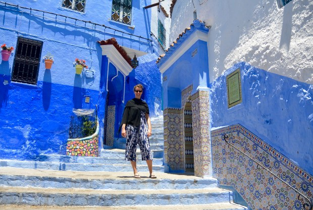 Brittany on a blue staircase in Chefchaouen
