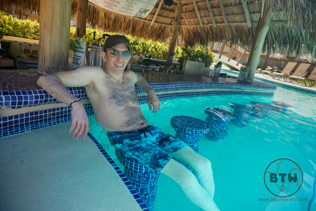 Aaron sitting at a pool-side bar at the Doubletree Resort in Puntarenas, Costa Rica | BIG tiny World Travel