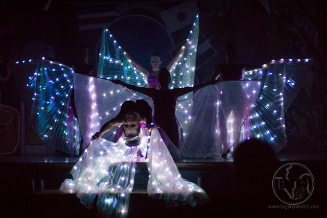 Three dancers posing with illuminated wings on a dark stage during a show at the Doubletree Resort in Puntarenas, Costa Rica | BIG tiny World Travel