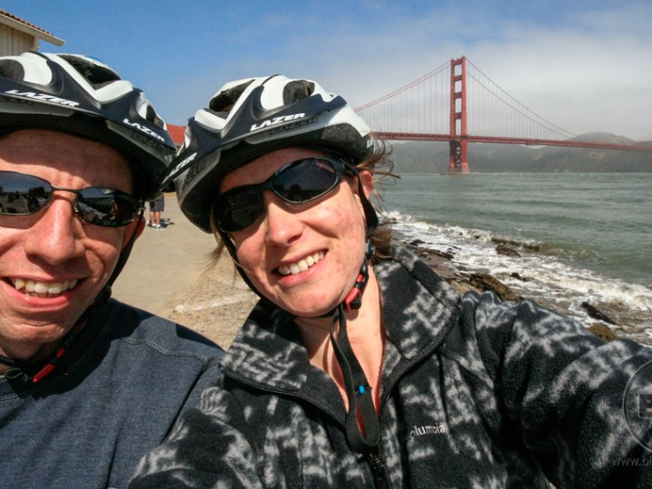 Aaron and Brianna wearing bike helmets in front of San Francisco's Golden Gate Bridge | BIG tiny World Travel