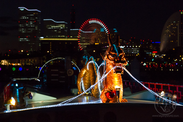 An illuminated serpentine dragon atop a boat in the harbor of Yokohama, Japan
