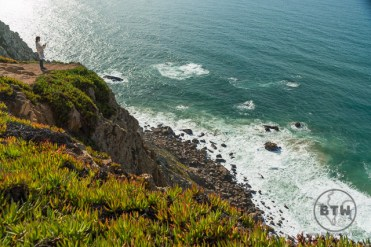 Woman standing on the cliff's edge at Cabo da Roca