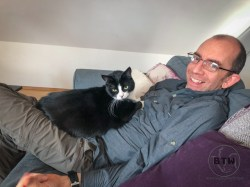Oscar the tux cat laying on top of Aaron in Basel, Switzerland