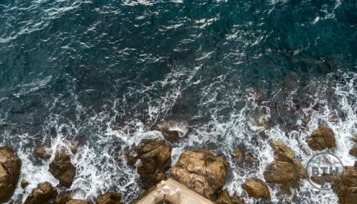 Waves lapping at the rocks at the base of the Dubrovnik wall in Croatia