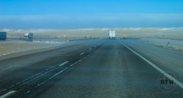 A truck on the highway in Idaho as wind blows snow across the road