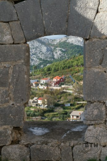 Looking at homes through a hole in a wall at Klis Fortress near Split, Croatia