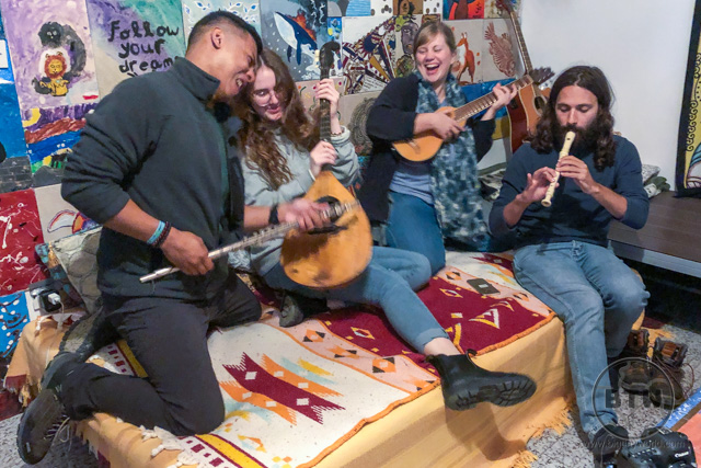 A group of people jokingly playing instruments in a hostel in Omis, Croatia