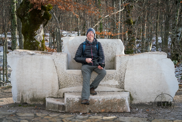 Aaron sitting in a large, stone throne at Plitvice Lakes National Park, Croatia