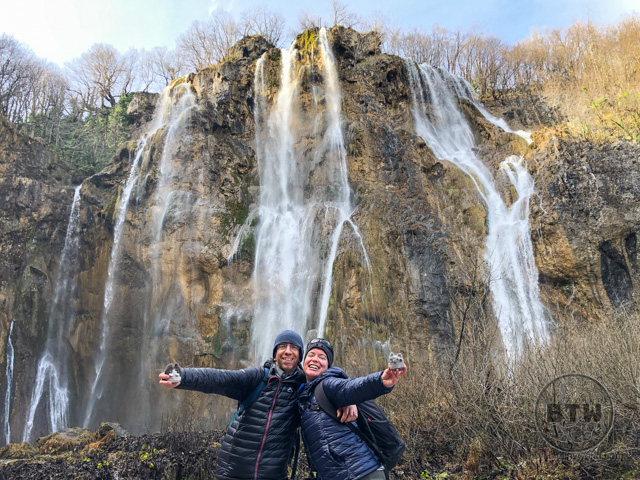 Aaron and Brianna with the travel kitties in front of a large waterfall in Plitvice Lakes National Park, Croatia