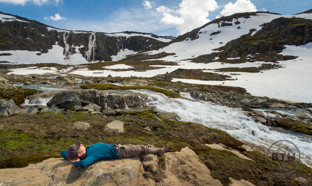 Aaron laying down in front of a snowy waterfall in Norway