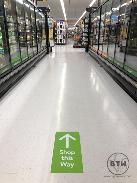 A grocery aisle denoting the direction shoppers should take