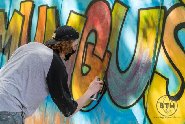 A man spray painting wall art in Portland, Oregon