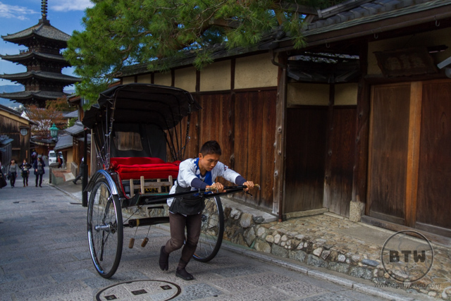 A man pushing an empty rickshaw up the hill in Kyoto, Japan