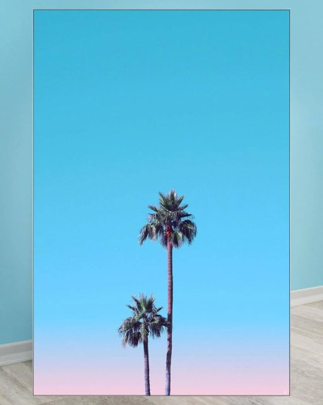 Large wall decor of two centered palm trees with a blue and pink sky.