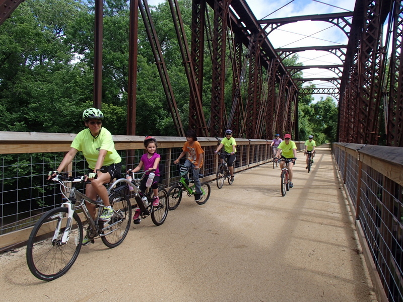 Riders on the historic railroad trestle bridge over Elm Creek on the Southwind Rail Trail.