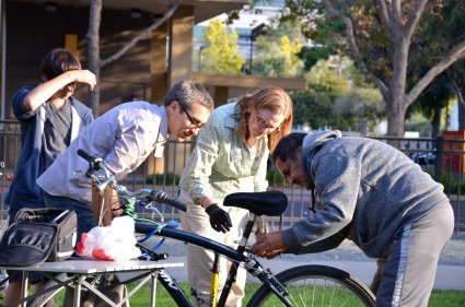 Bike Tent principal mechanic Bronwen Mauch (wearing glove) instructs a Bike Tent client and Bike Concord volunteers on a repair job.
