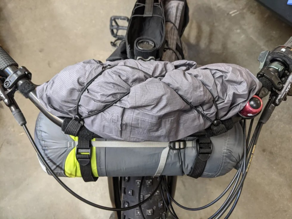 """A """"hardshell"""" rain jacket strapped to the top of the loop with the adjustable integrated elastic cord system."""